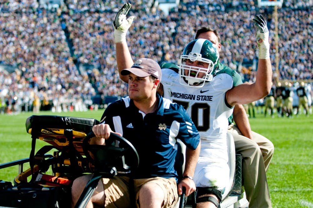 Redshirt freshman offensive tackle Skyler Burkland leaves the game after an injury in the first half. The Spartans lost to the Fighting Irish, 31-13, on Saturday afternoon at Notre Dame Stadium in South Bend, Ind. Josh Radtke/The State News