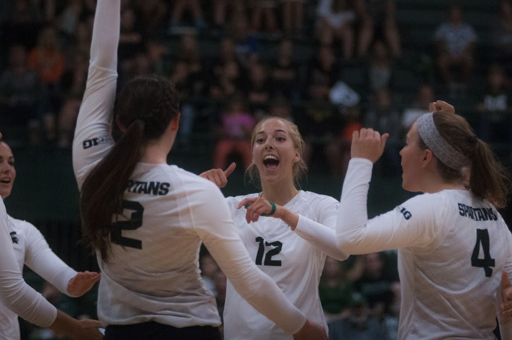 Junior setter Rachel Minarick (12) celebrates with her teammates during the volleyball game against Notre Dame on Sept. 16, 2016 at the Jenison Field House. The Spartans defeated the Fighting Irish, 3-0.