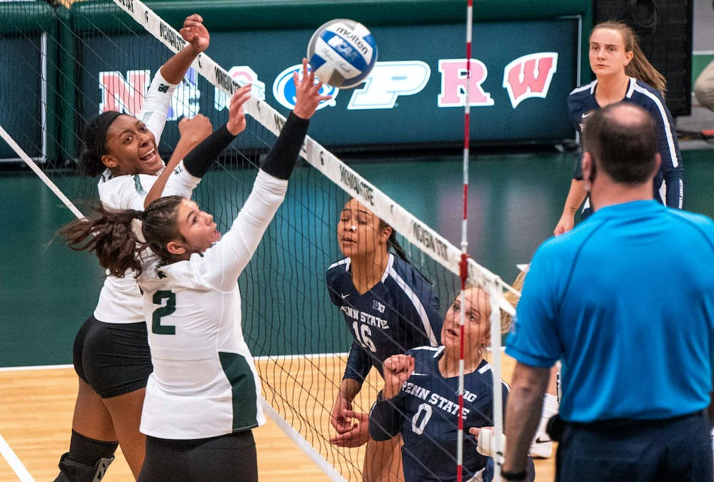 <p>Freshman setter Celia Cullen (2) and junior middle blocker Naya Gros (17) block the ball in the first set against Penn State. The Nittany Lions shut out the Spartans, 3-0, on March 20, 2021. </p>