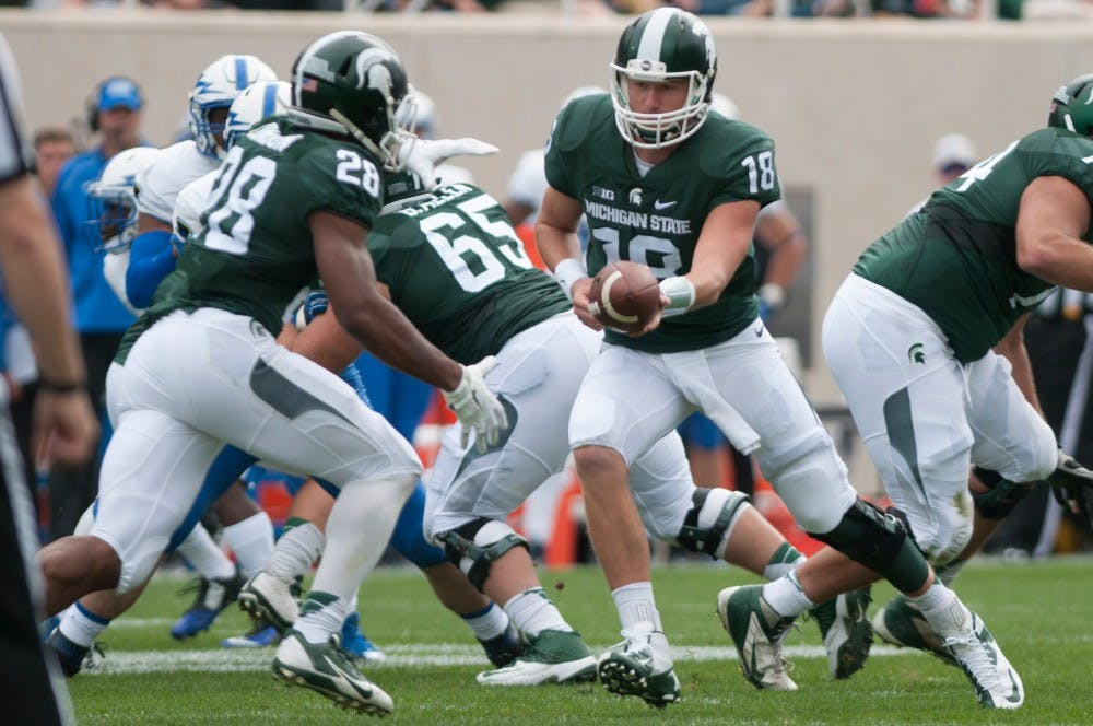<p>Senior quarterback Connor Cook, 18, hands off the ball to redshirt freshman running back Madre London, 28, in the first half during the game against Air Force on Sept. 19, 2015 at Spartan Stadium. The Spartans defeated the Falcons, 35-21. Kennedy Thatch/The State News</p>