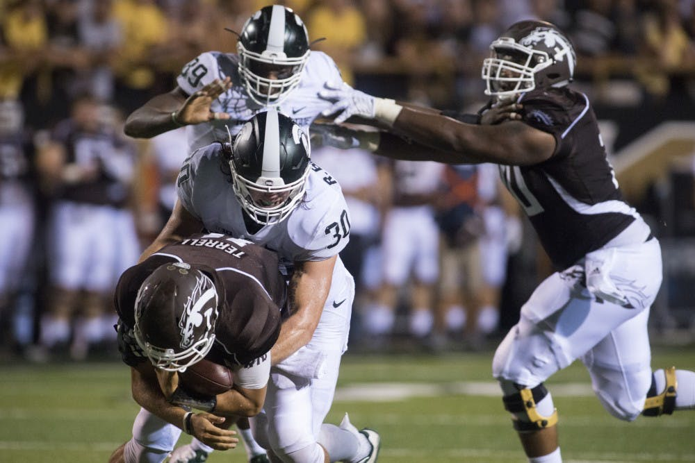 <p>Junior linebacker Riley Bullough sacks Western Michigan quarterback Zach Terrell on during a game against Western Michigan on Sept. 4, 2015 at Waldo Stadium in Kalamazoo, Michigan. The Spartans beat the Broncos, 37-24. Julia Nagy/The State News</p>