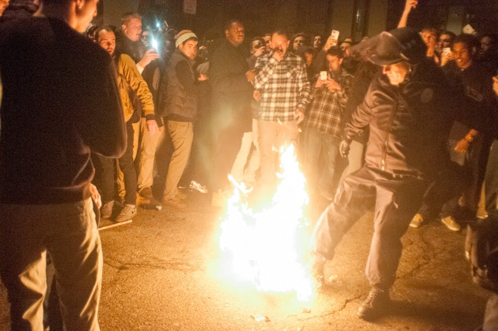 A police officer goes to stomp out a fire started by a student  after MSU's victory over Iowa on Dec. 5th, 2015, at Cedar Street.