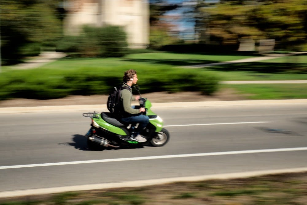 <p>An MSU student drives a moped in front of the MSU Library on October 23, 2019. </p>