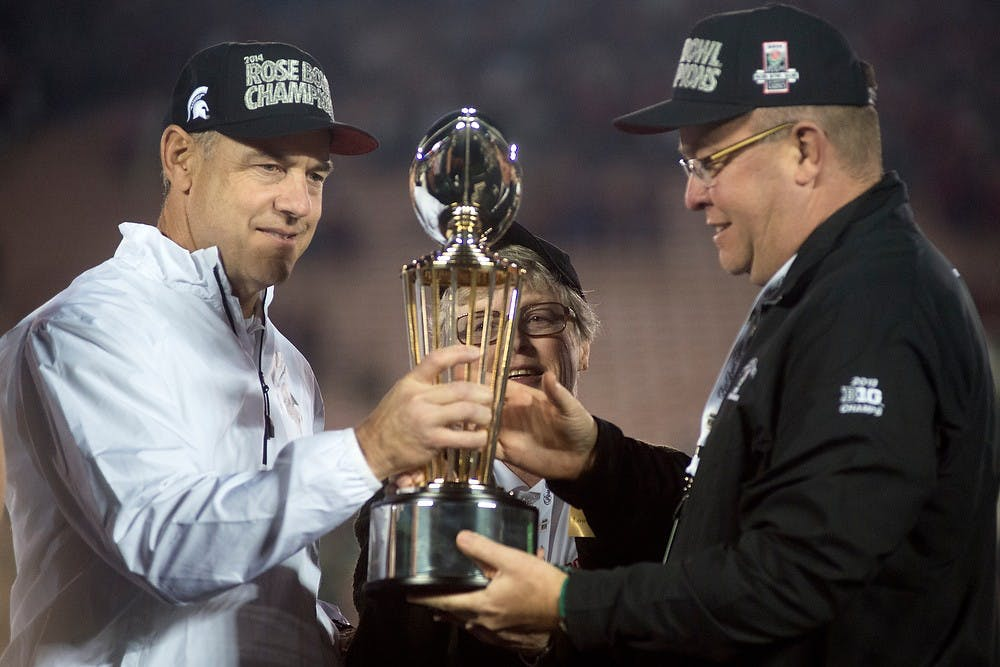<p>Head coach Mark Dantonio, left, MSU president Lou Anna K Simon and athletic director Mark Hollis hold the trophy after the 100th Rose Bowl game against Stanford on Jan. 1, 2014, in Pasadena, Calif. The Spartans defeated the Cardinals, 24-20. Julia Nagy/The State News</p>
