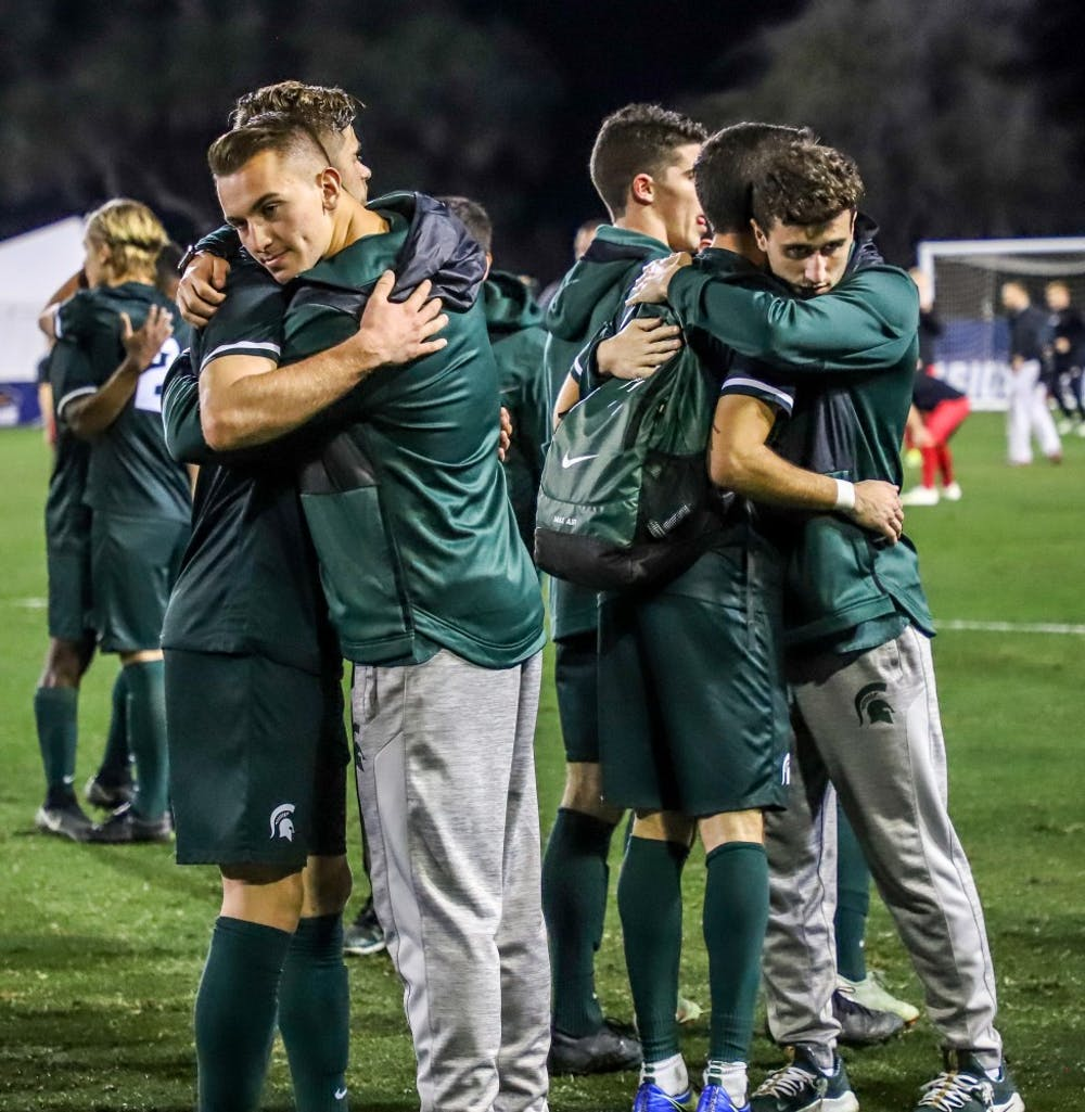 Spartan Players hug eachother after the game against Akron on Dec. 7, 2018 at Harder Stadium. The Spartans fell to the Zips 5-1.