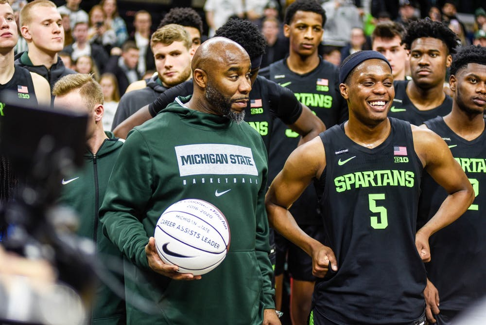 Former MSU basketball player Mateen Cleaves, left, and senior guard Cassius Winston (5), right, stand together as Cassis is recognized for having the most assists in his career at 817 during the game against Wisconsin at Breslin Center on Jan. 17, 2020.The Spartans defeated the Badgers, 55-67.