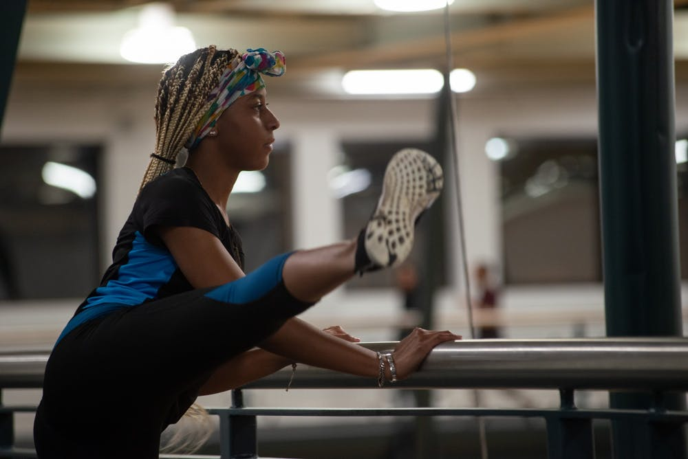 <p>President of BGF, Jasmine Parker, stretches after warming up on the indoor track on Feb. 3, 2020 at IM Sports East.</p>