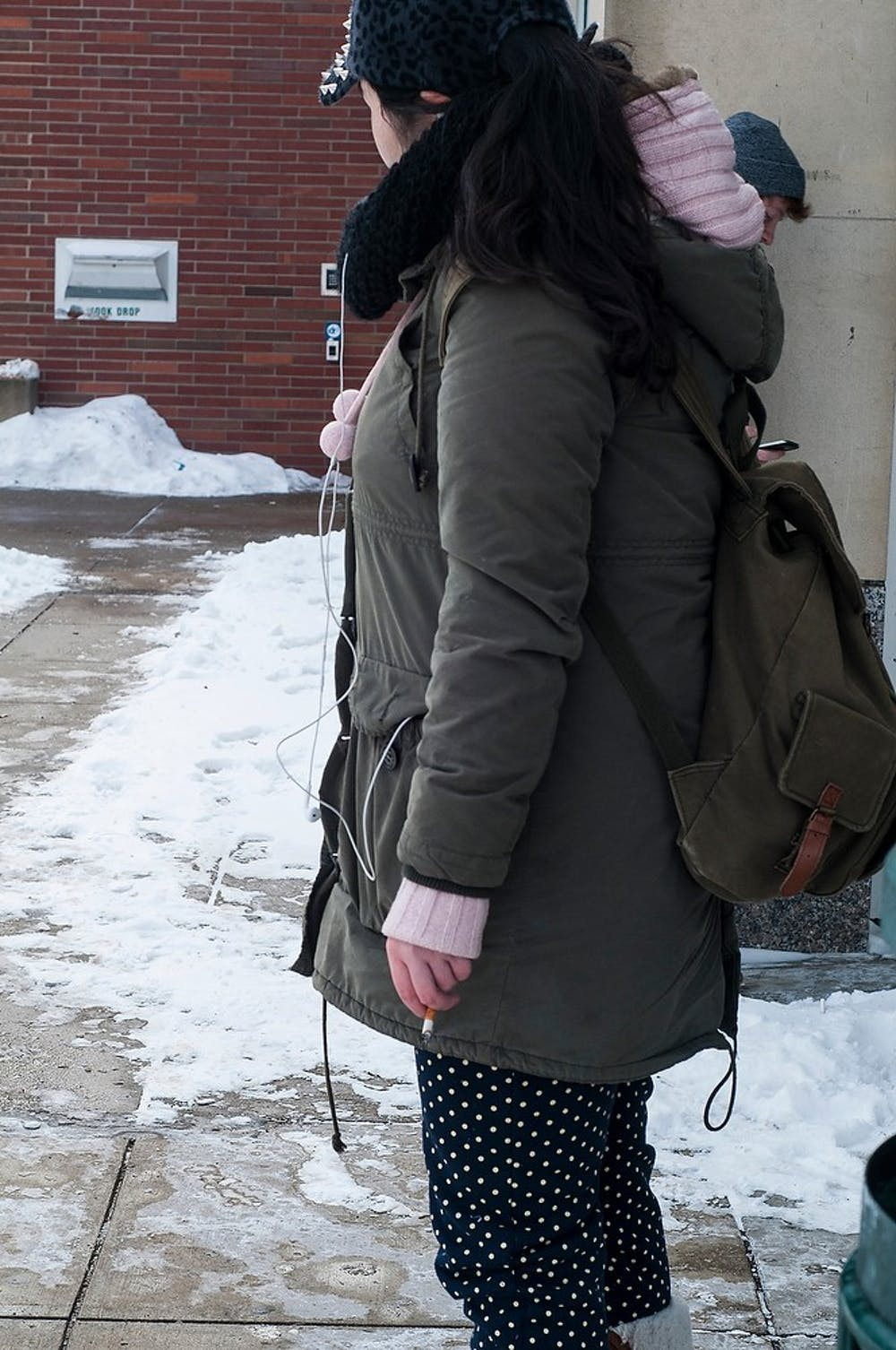 <p>Finance junior Michelle Jing smokes a cigarette Feb 16, 2015, outside of the MSU Library. Michelle is an international student and says a tobacco ban on campus will create more exclusivity for international students. Hannah Levy/The State News</p>