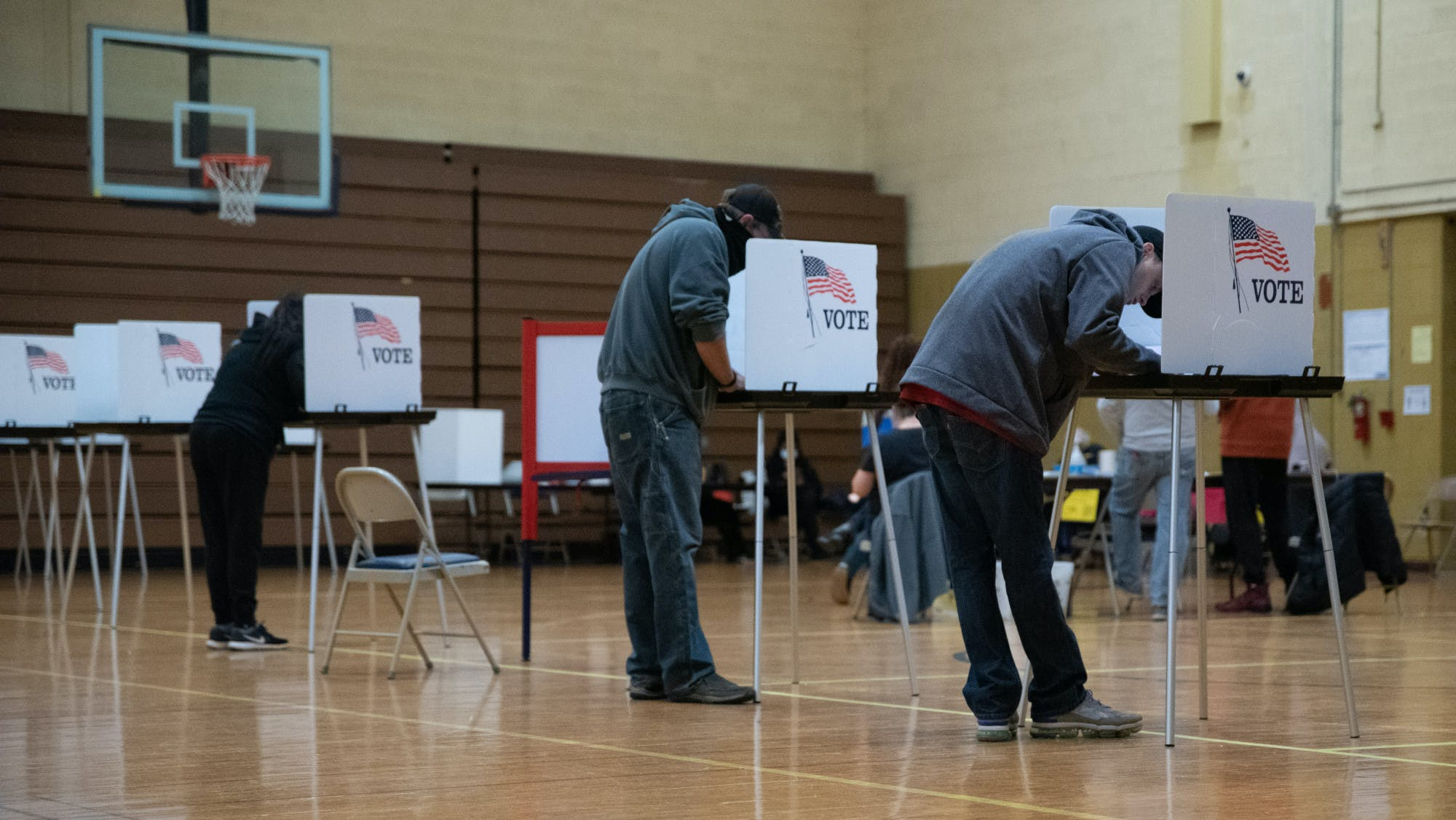 Three people lean into voting booths.