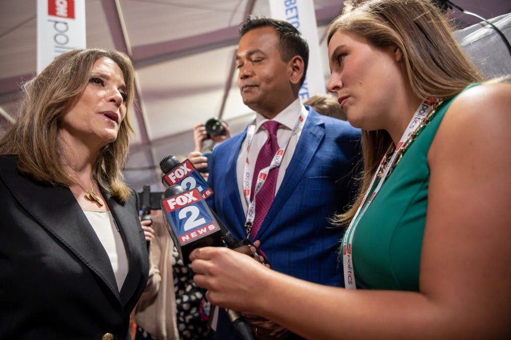 Author Marianne Williamson (left) speaks to Fox 2 Detroit's Roop Raj (center) and Jessica Dupnack (right) after the first night of CNN's Democratic Debates at Detroit's Fox Theater on July 30, 2019.