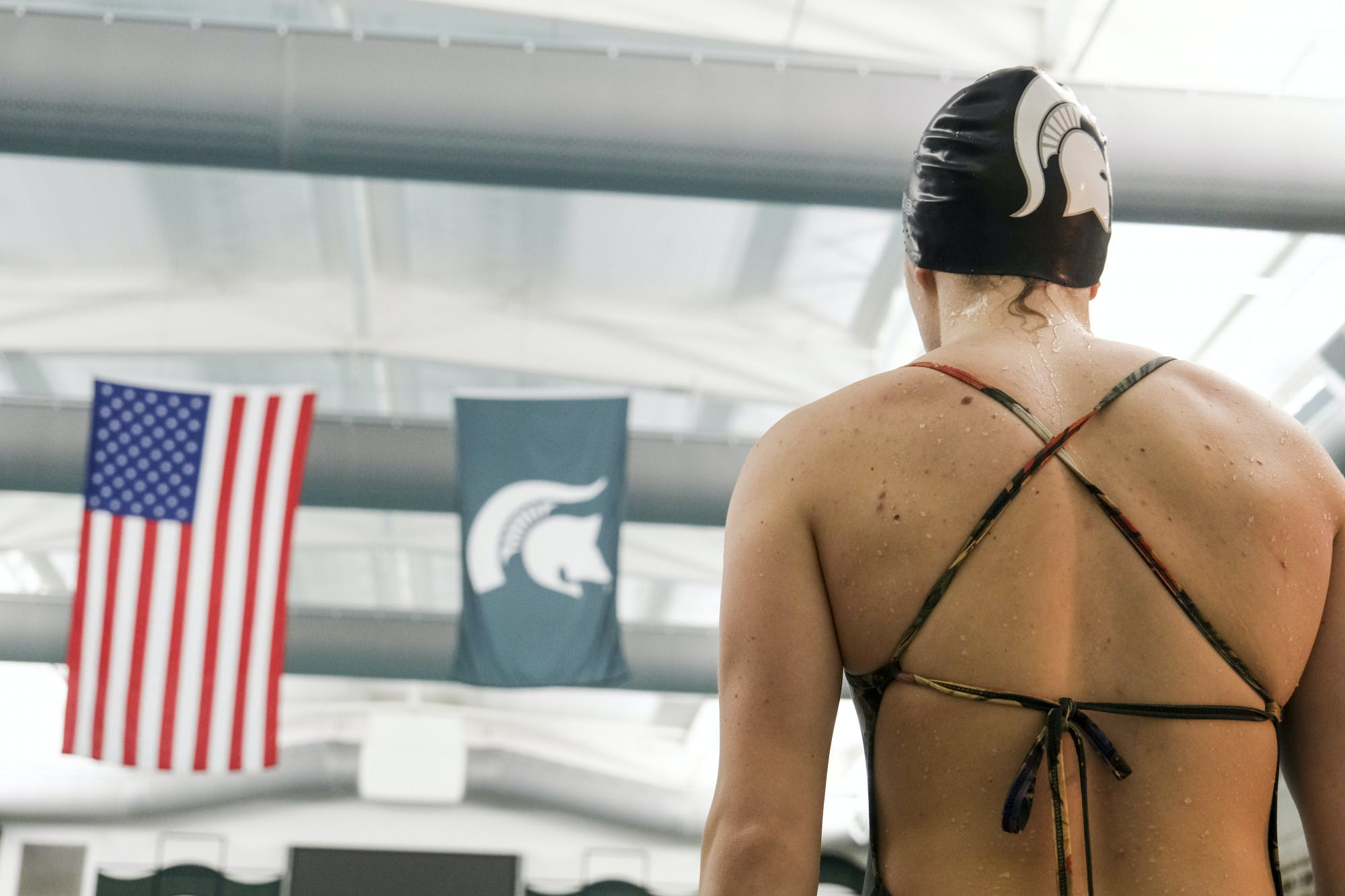 A person wearing a swimsuit and a swim cap with the Michigan State Spartans logo on it stands with their back to the camera, facing an American flag and a flag with the Michigan State Spartans logo on it that hang from the rafters.