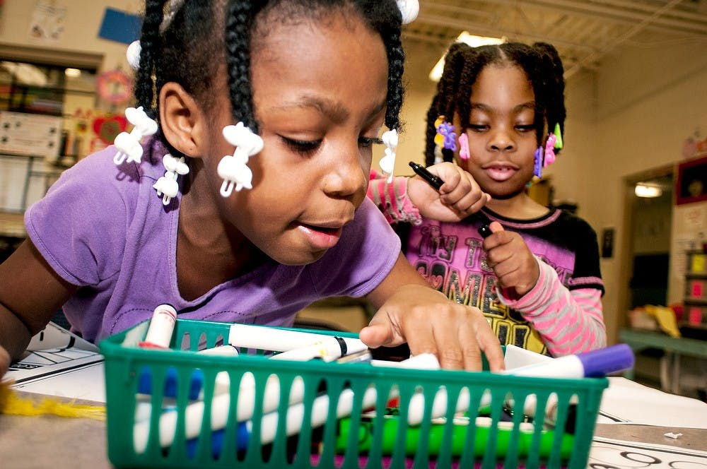 <p>Lansing resident Samarya Lampkins, 8, left, looks for a marker while Zamaria Hawkins, 6, prepares to color a picture on Saturday, Feb. 23, 2013, at the Boys and Girls Club of Lansing.  Not only is there an arts and crafts room in the building, but also a gym, computer room and junior room.</p>