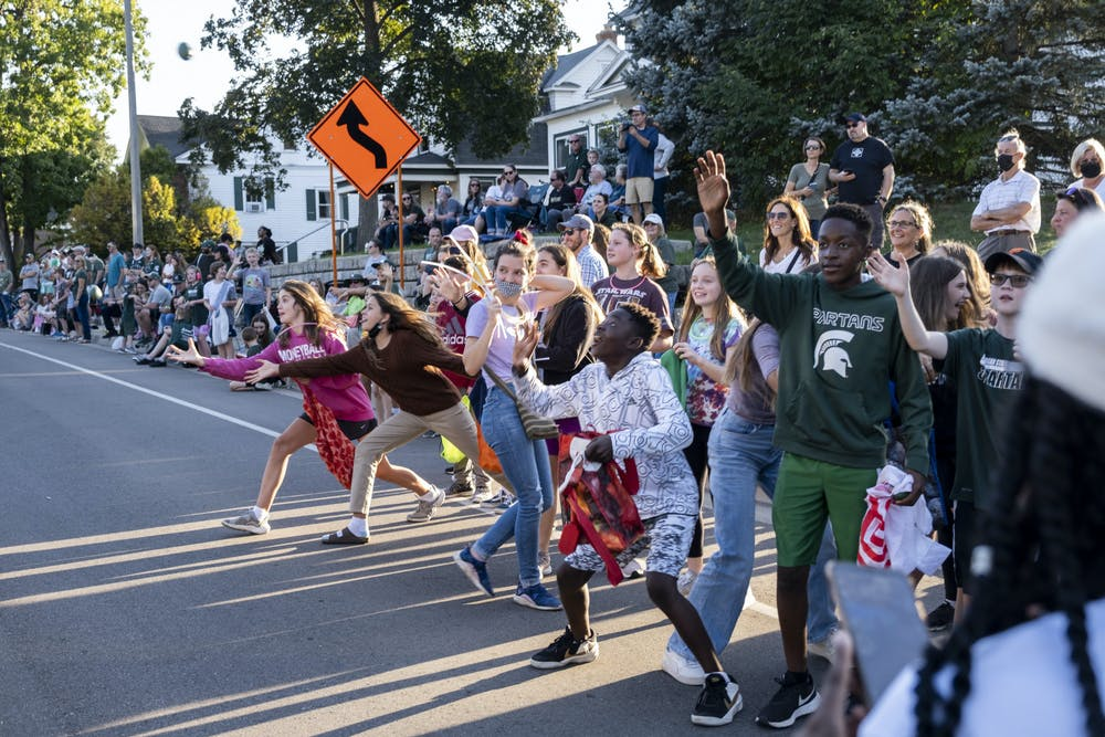 Parade spectators reaching for the tossed candy at the MSU Homecoming parade on October 1, 2021, on Farm Lane in East Lansing.