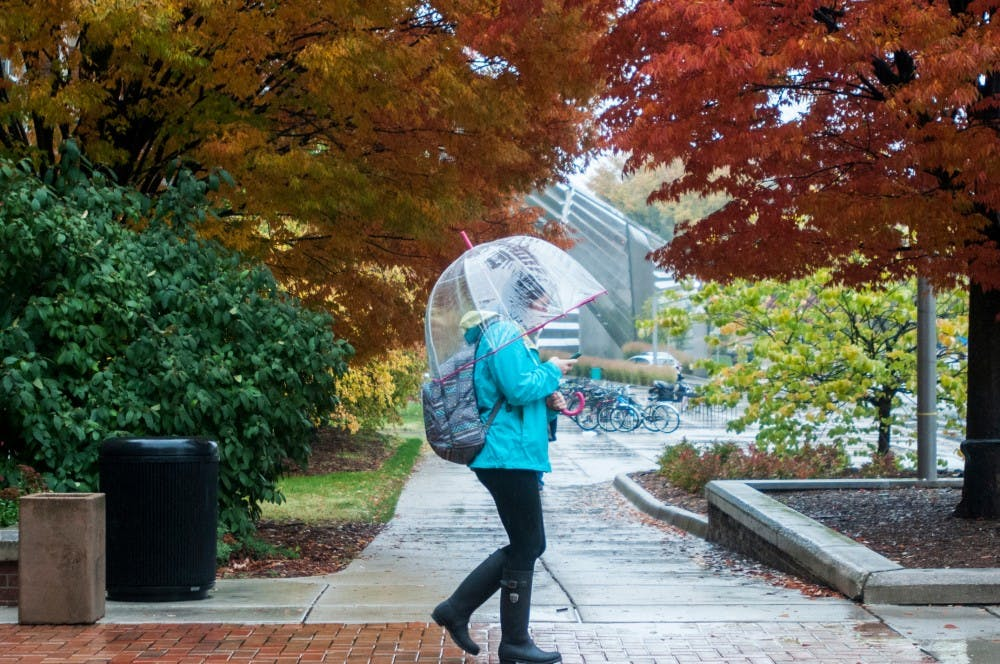<p>A student leaves Berkey Hall in October 2013. According to PureMichigan.com, mid to late October is the best time to see the fall colors in the lower peninsula. </p>