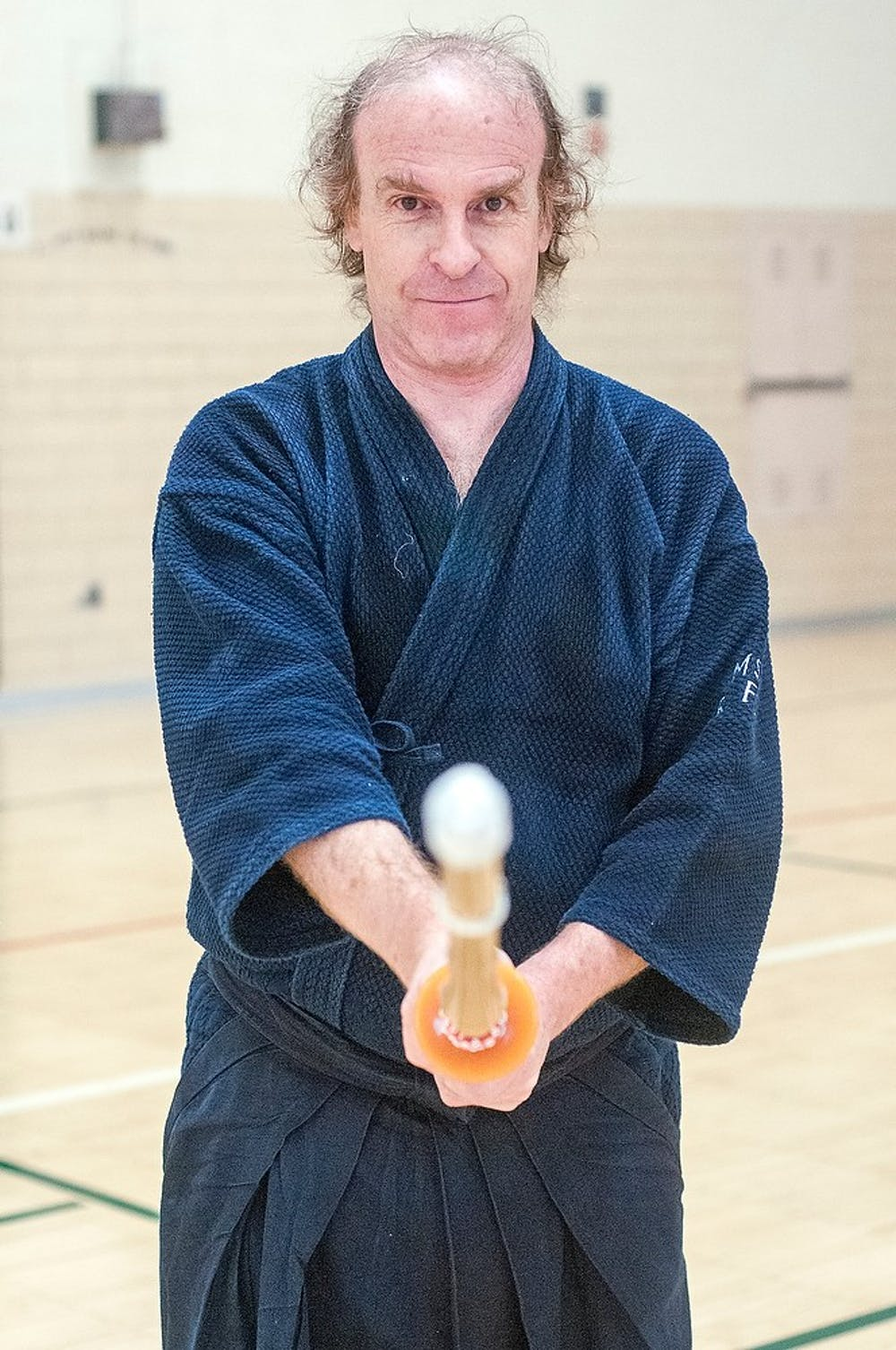 <p>MSU alumn and Senior Physicist at the National Superconducting Cyclotron Laboratory Ron Fox poses for a portrait with his shinai Feb. 9, 2015, in the IM Sports-Circle gymnasium. Fox started practicing kendo in college and now volunteers instructing KIN 102M, Kendo I. Kelsey Feldpausch/The State News</p>