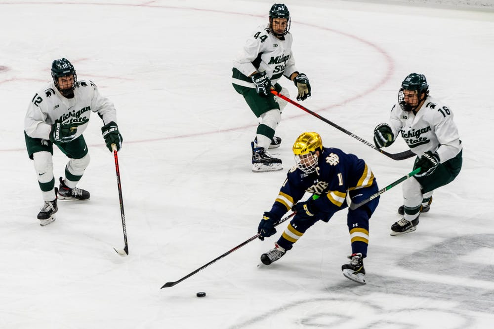 <p>Notre Dame right wing Cal Burke (11) avoids three Michigan State Defenders. The Spartans were defeated by the Fighting Irish, 2-1, at Munn Ice Arena on November 22, 2019. </p>