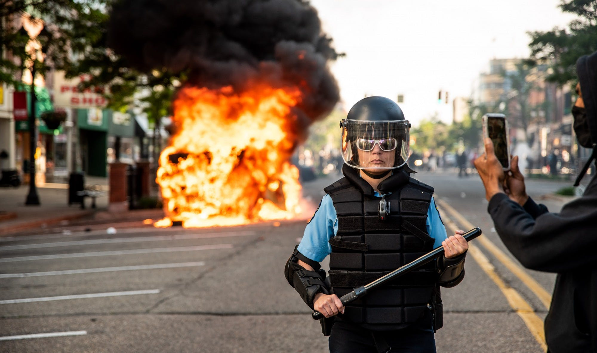 A person wearing riot gear and sunglasses holds a baton and stands in the middle of the road while a car burns in the background. Another person wearing a face mask holds up their phone.