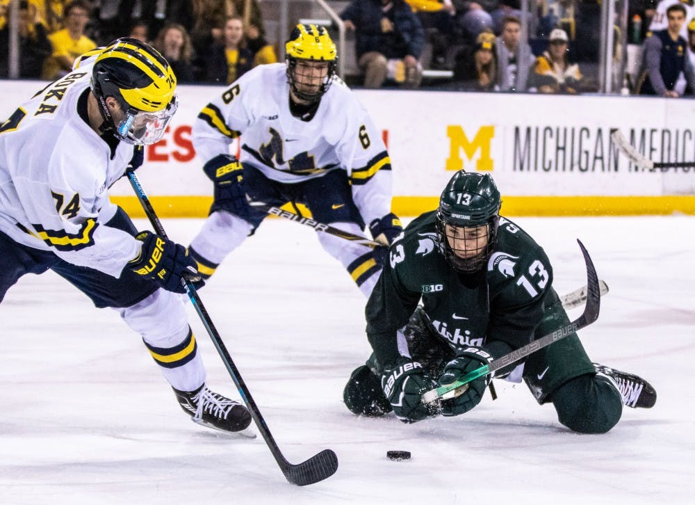 Senior forward Brennan Sanford (13) swings at the puck from his knees during the game against Michigan Feb. 9 at Yost Ice Arena. The Spartans fell to the Wolverines, 5-3.