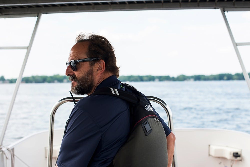 <p>Sport Facility Professional with the Department of Recreational Sports and Fitness services Ken Warshaw steers a boat June 26, 2014, on Lake Lansing. Warshaw has held his position for over 18 years. Hayden Fennoy/The State News</p>