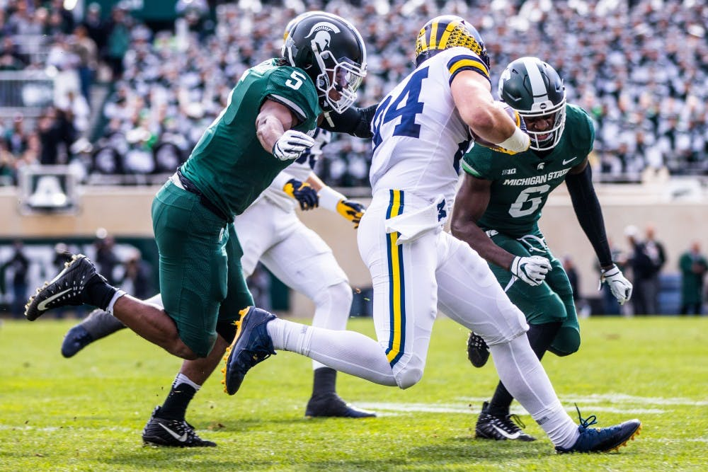 <p>MSU defenders Andrew Dowell (5) and David Dowell (6) tackle Michigan tight end Sean McKeon (84) during the game at Spartan Stadium Oct. 20. The Wolverines defeated the Spartans, 21-7.</p>