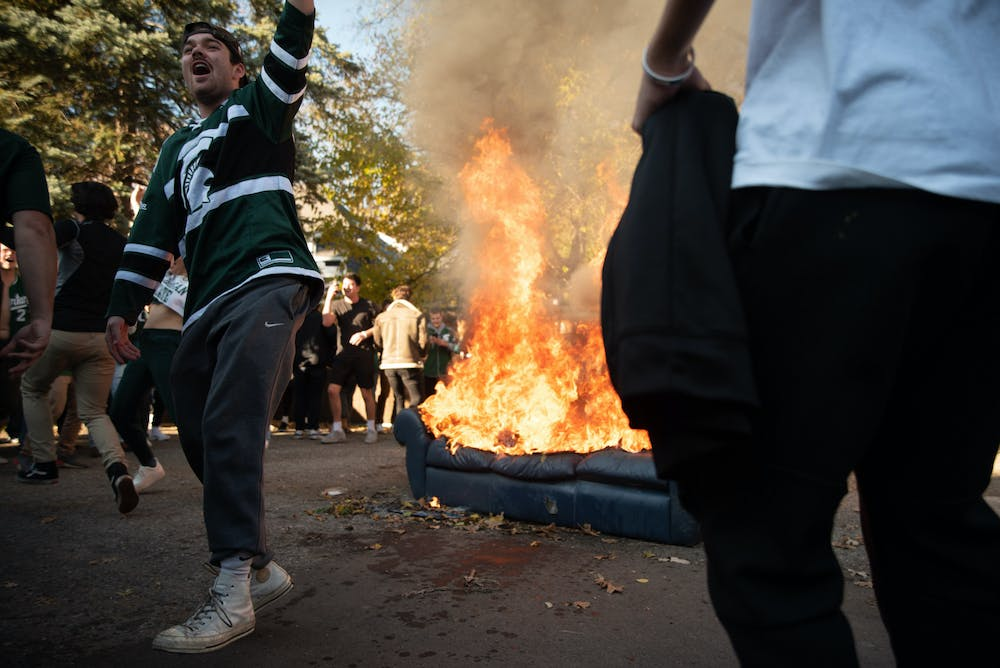 <p>Michigan State University students partying near a burning couch in an alley off of Division Street on Oct. 31, 2020.</p>