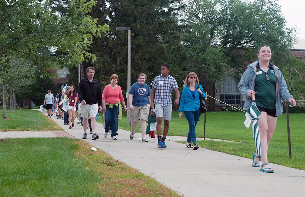 <p>An AOP leader gives a tour of MSU to a group of incoming students and their parents July 7, 2015 on Chestnut Road. Catherine Ferland/ The State News </p>