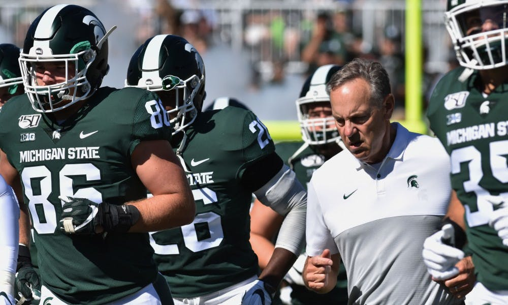 <p>Coach Mark Dantonio runs out with his team to start the game off against Arizona State. The Spartans fell to the Sun Devils, 10-7, on Sept. 14, 2019 at Spartan Stadium.</p>