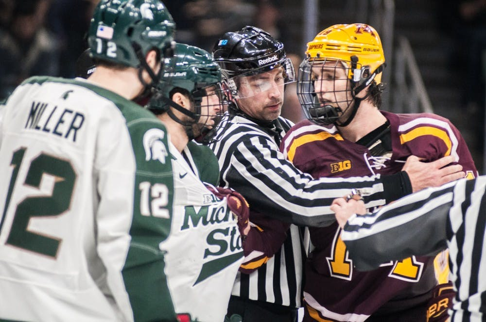 A referee puts his arms between players during the game against Minnesota on Jan. 18, 2018 at Munn Ice Arena. The Spartans fell to the Gophers 5-4.