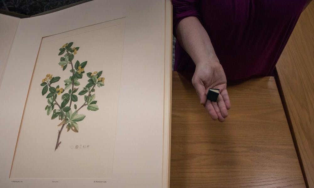 """Ruth Ann Jones, the special collections education and outreach librarian, holds the library's smallest book next to the largest book at the Special Collections Seminar Room at the Main Library on Jan. 11, 2019. The largest book, """"Banks' Florilegium"""", was published in 1981. The smallest book, """"An Alphabet Book"""", was published in 1980."""