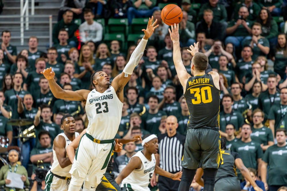 <p>Iowa guard Connor McCaffery (30) shoots over junior forward Xavier Tillman Sr. (23). The Spartans defeated the Hawkeyes, 78-70, at the Breslin Center on Feb. 25, 2020. </p>