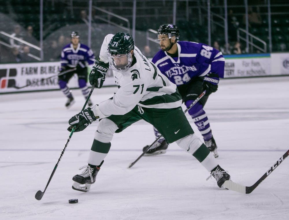 <p>Senior forward Logan Lambdin (71) takes the puck up the ice during the game against Western Ontario at Munn Ice Arena Oct. 7, 2019. The Spartans defeated the Mustangs, 6-1.</p>
