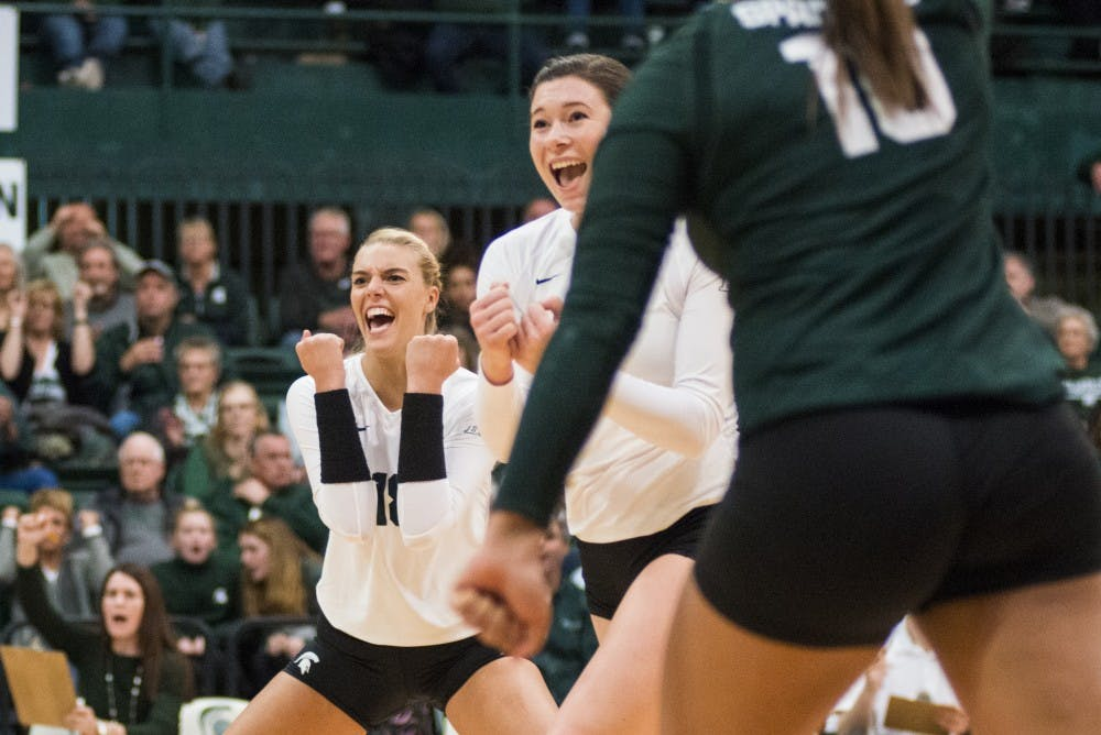 From left to right, junior outside hitter Holly Toliver (18), redshirt junior outside hitter Autumn Bailey (2) and junior libero Abby Monson (10) celebrate after scoring a point during the first round of the NCAA Championship against Fairfield University on Dec. 2, 2016 at Jenison Field House.