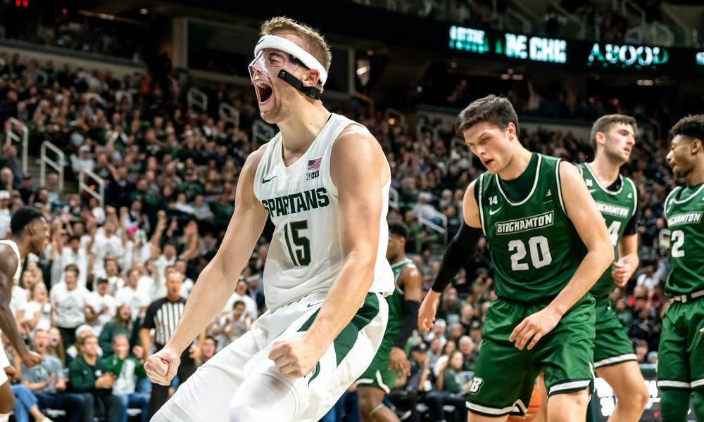 <p>Junior forward Thomas Kithier (15) celebrates after a dunk against Binghamton. The Spartans defeated the Bearcats 100-47 at the Breslin Student Events Center on Nov. 10, 2019. </p>