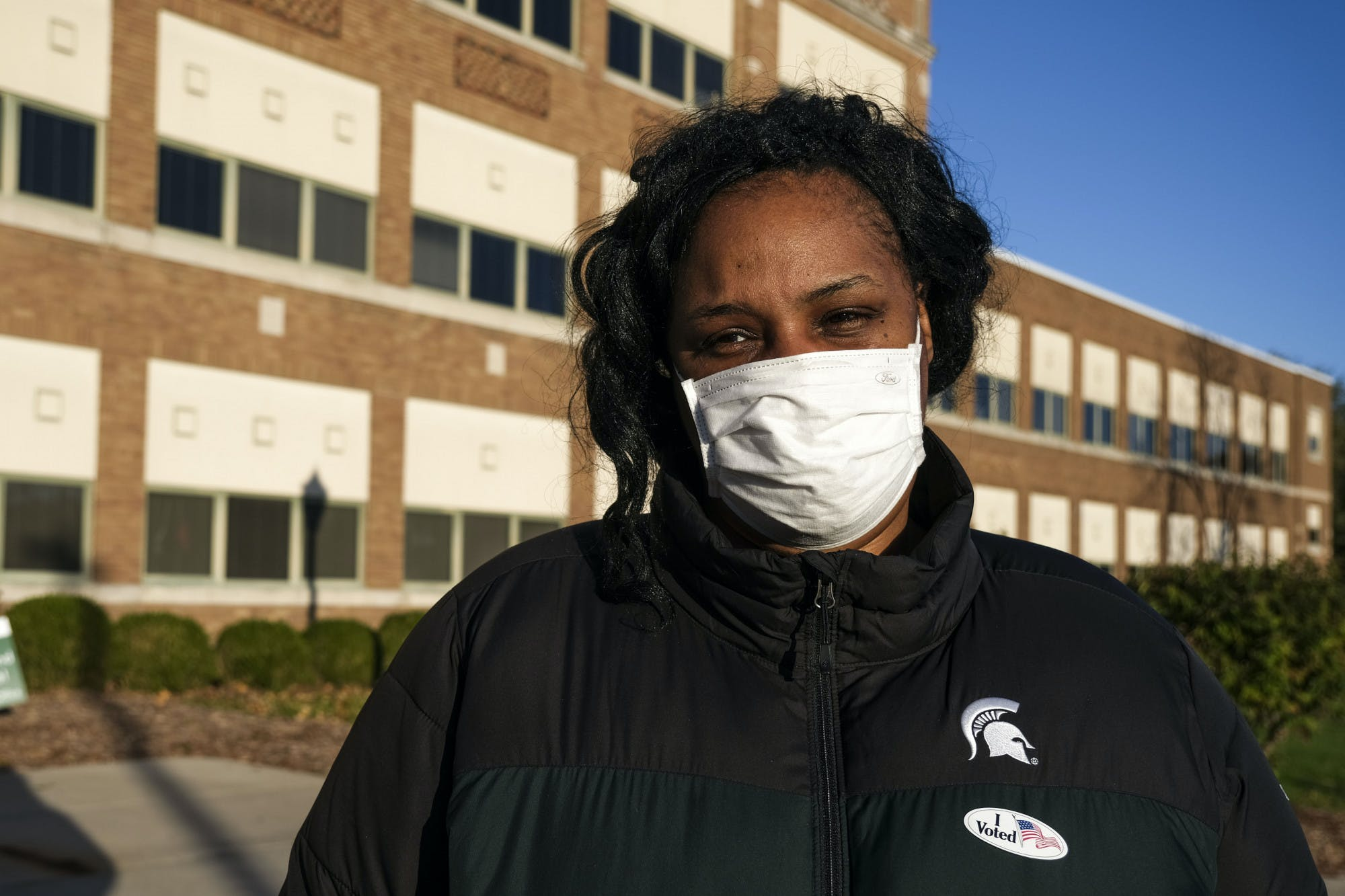 A person wearing a face mask and an 'I voted' sticker poses for a portrait.