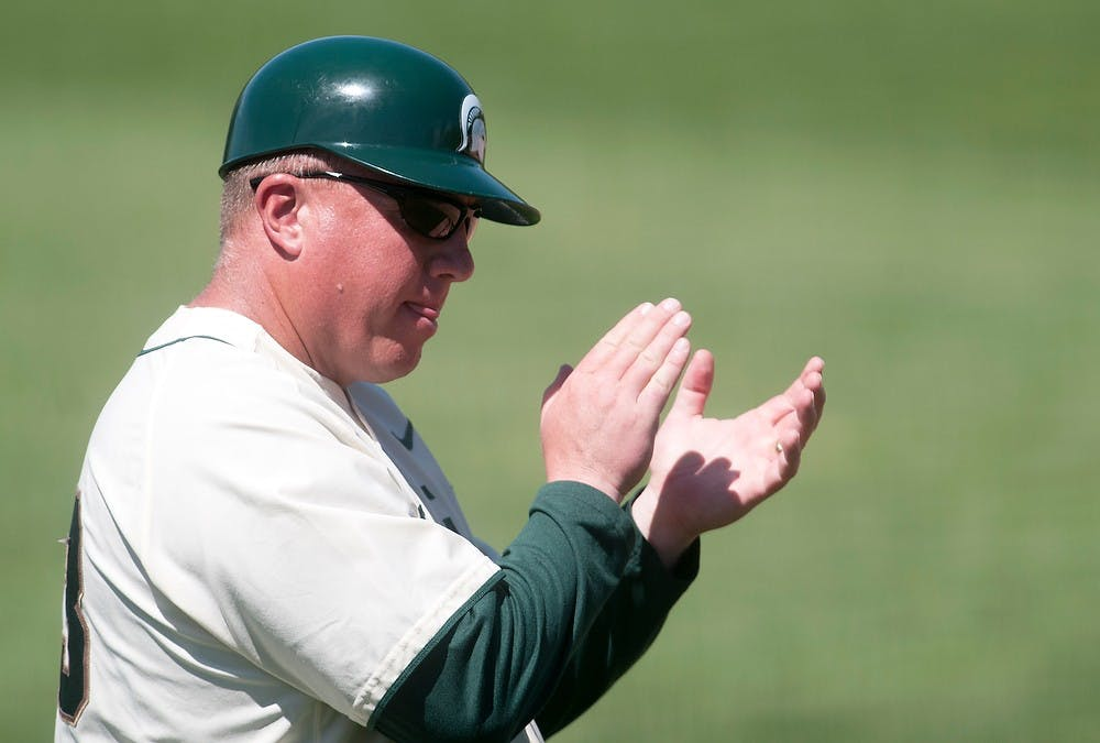 <p>Men's baseball coach Jake Boss Jr. encourages players from third base in the third game of the series against the University of Illinois on May 5, 2013, at McLane Baseball Stadium at Old College Field. The Spartans won 4-3 after trailing 3-1 for a majority of the game. Danyelle Morrow/The State News</p>