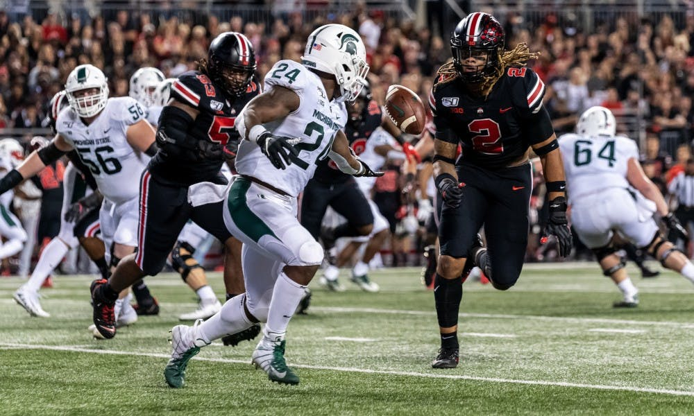 <p>Then-freshman running back Elijah Collins (24) fumbles a pitch from then-senior quarterback Brian Lewerke against Ohio State. The Buckeyes defeated the Spartans, 34-10, on Oct. 5, 2019, at Ohio Stadium.</p>