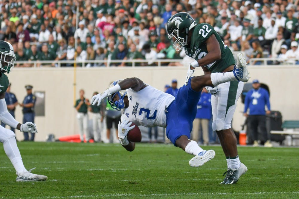 <p>Junior cornerback Josiah Scott (22) tackles a Tulsa wide receiver at Spartan Stadium Aug. 30, 2019. The Spartans defeated the Golden Hurricane, 28-7.</p>