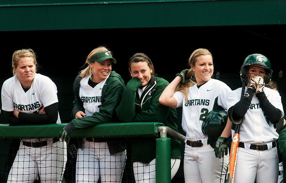 """<p>Members of the <span class=""""caps"""">MSU</span> softball team smile in the dugout at a player on the field during the game against Michigan, April 14, 2013, at Secchia Stadium at Old College Field. Katie Stiefel/The State News</p>"""