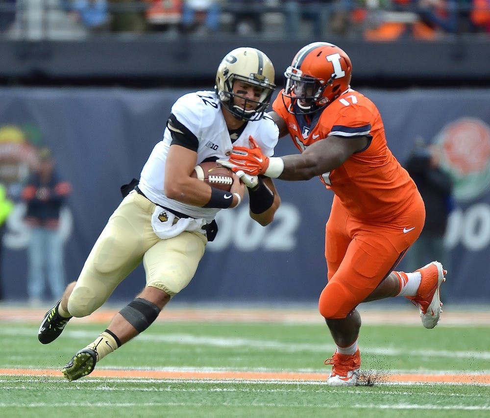 <p>Purdue sophomore quarterback Austin Appleby pushes through Illinois defensive lineman Jihad Ward on Saturday at the University of Illinois Memorial Stadium. Photo Courtesy of Purdue Exponent</p>