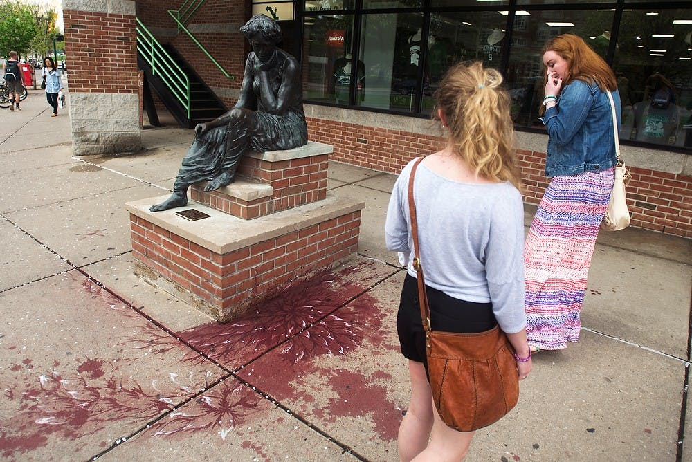 <p>Education junior Kenna Holsington, left, and Caitlin Hamilton, right, observe a public art display May 12, 2014, on Grand River Ave., in front of Bubble Island. The art was created by Pakistani artist Imran Qureshi in locations throughout East Lansing. Hayden Fennoy/The State News</p>