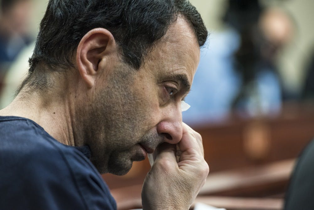 "Ex-MSU and USA Gymnastics Dr. Larry Nassar wipes away tears during Christina Barba's statement on the sixth day of his sentencing on Jan. 23, 2018 at the Ingham County Circuit Court in Lansing. ""I forgive you Larry,"" Barba said. ""I will never hate you."" (Nic Antaya 