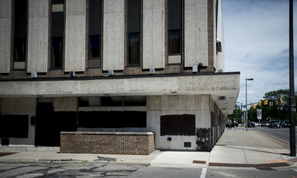 <p>An empty building is pictured at the corner of Grand River Avenue and Abbot Road on June 6, 2017. The building has since been demolished, and the remaining site is part of the Park District redevelopment project.</p>