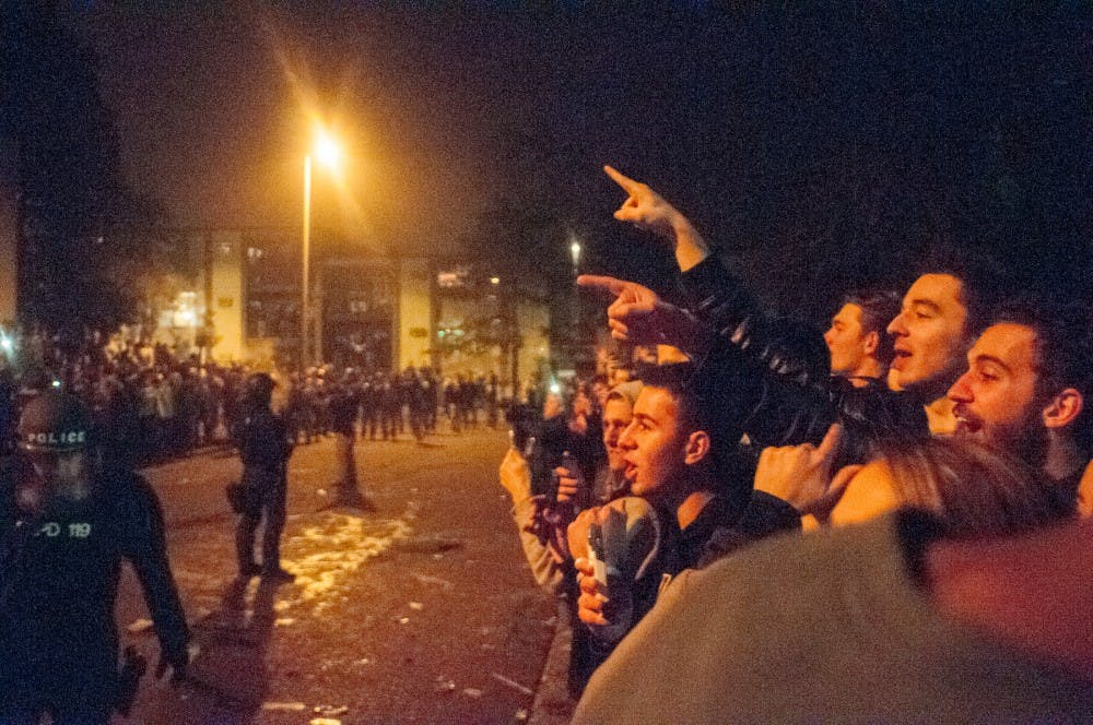 Students yell at the police officers after MSU's victory over Iowa on Dec. 5th, 2015, at Cedar Street celebration.