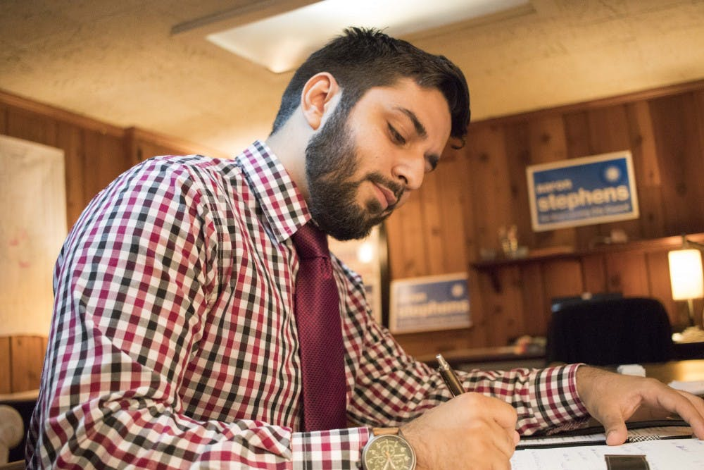 <p>Aaron Stephens writes some notes on Sept. 13, at his house on Kedzie Street. Stephens is running for East Lansing City Council.</p>