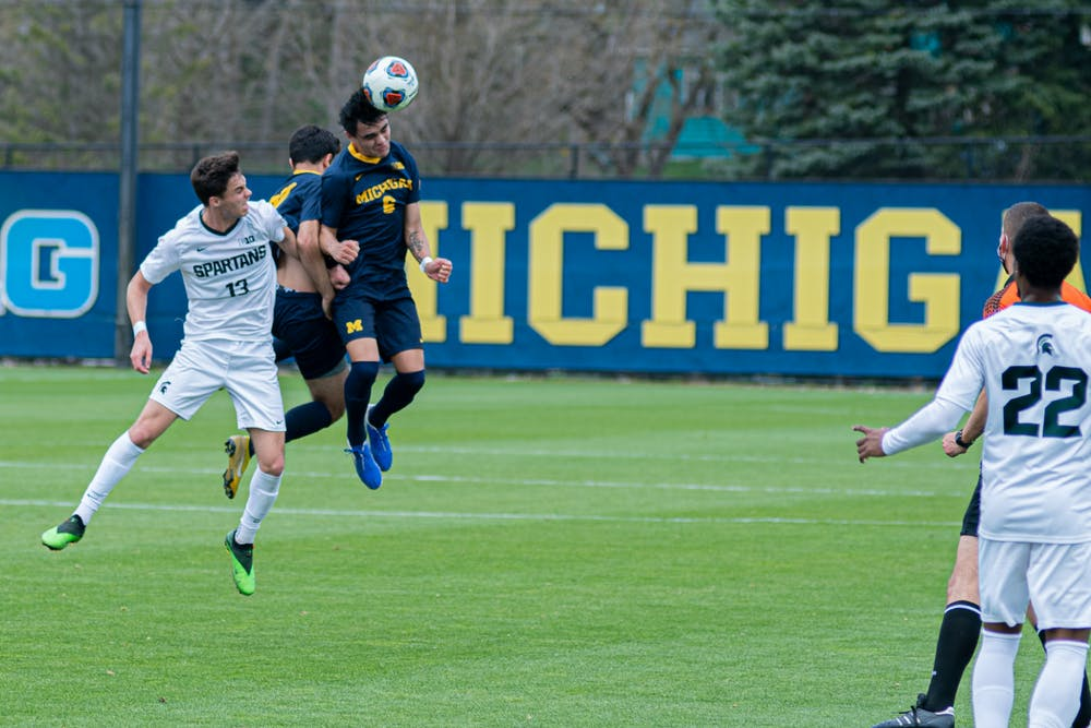 <p>Freshman midfielder Quin Rodgers (6) heads the ball on April 10, 2021, during the Wolverines&#x27; 1-0 victory against the Spartans.</p>