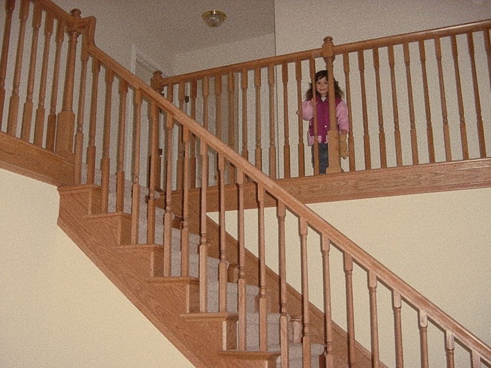 <p>Culture reporter Sara Tidwell, circa 2003, standing behind the banister of her new home, one hand clutched to the wood and one hand clutched to a teddy bear. Photo courtesy of Craig Tidwell.</p>
