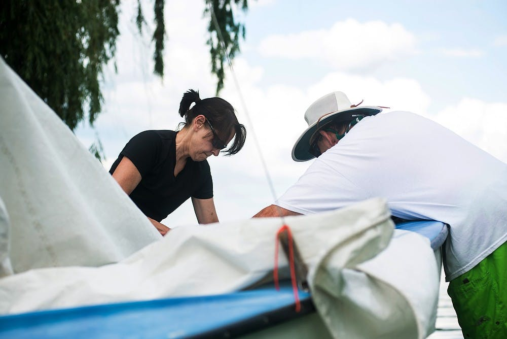 <p>From left, Portland, Mich., resident Chris Flaga and Lansing resident Gary Bush prepare a boat for sail June 26, 2014, at the Sailing Center off the shore of Lake Lansing. Flaga and Bush were both grateful for the windy day on the last day of class. Hayden Fennoy/The State News</p>