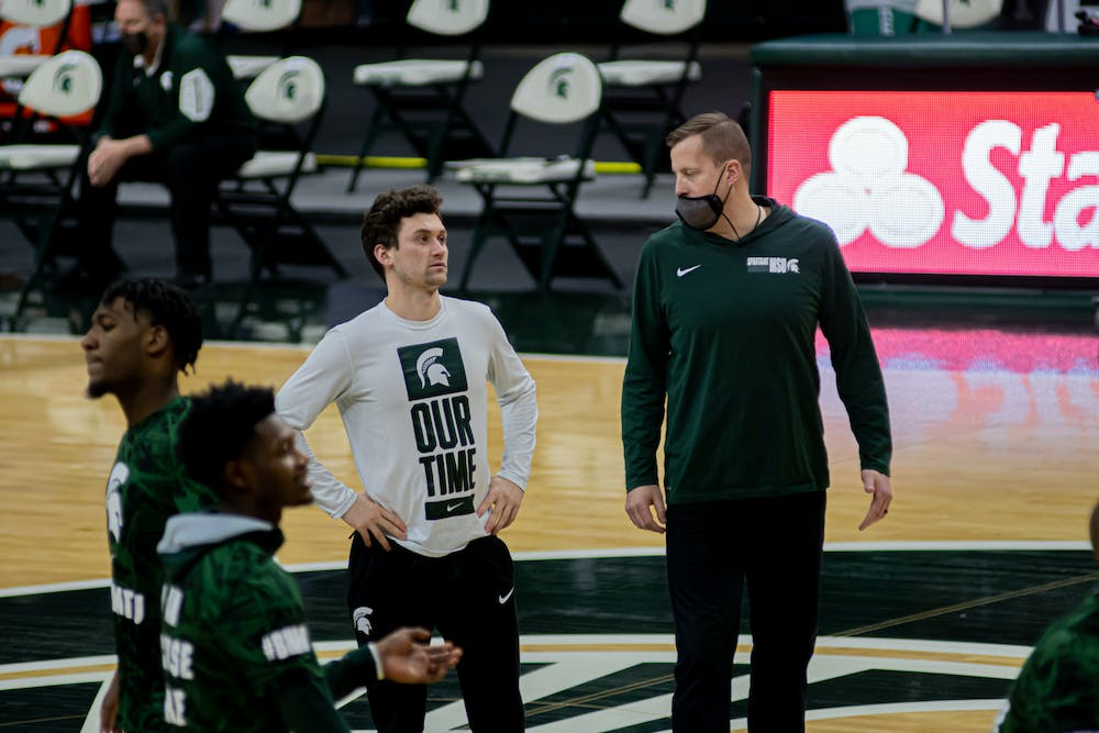 <p>Junior guard Foster Loyer watches the team warm up on Feb. 23, 2021. Loyer was inactive as a player, but helped his team from the bench in the win.</p>