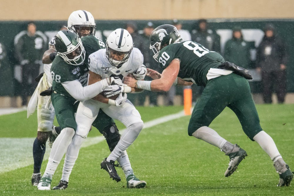 <p>Redshirt freshman tight end Trenton Gillison (88) and redshirt senior tight end Matt Seybert (80) tackle a Penn State defender after a blocked field goal during the game against Penn State Oct. 26, 2019 at Spartan Stadium. The Spartans fell to the Nittany Lions, 28-7.</p>