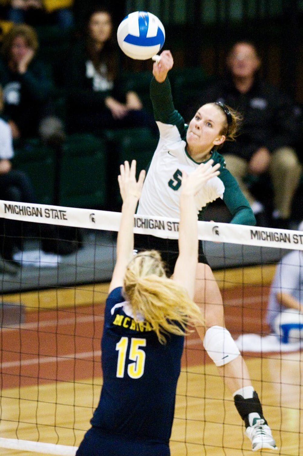 Senior outside hitter Jenilee Rathje hits the ball over Michigan middle blocker Courtney Fletcher Wednesday at Jenison Field House. The Spartans defeated the Wolverines 3-1. Matt Radick/The State News
